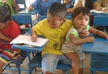 Niño lleva a su hermanito a sus clases por no tener quien lo cuide