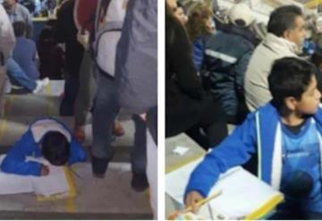 Niño lleva su tarea hasta un partido de futbol