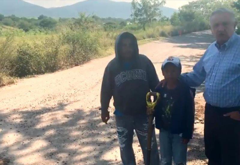 AMLO platica con niño que se gana la vida tapando baches en Morelos