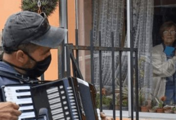 Toca el acordeón frente a la ventana de sus padres para animarlos en la cuarentena